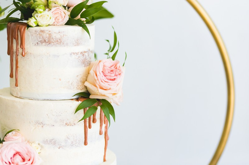 Pink rose on side of wedding cake