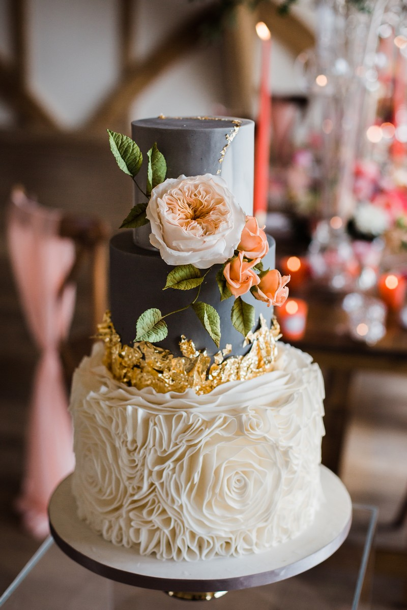 Grey and white wedding cake with coral flowers and gold leaf