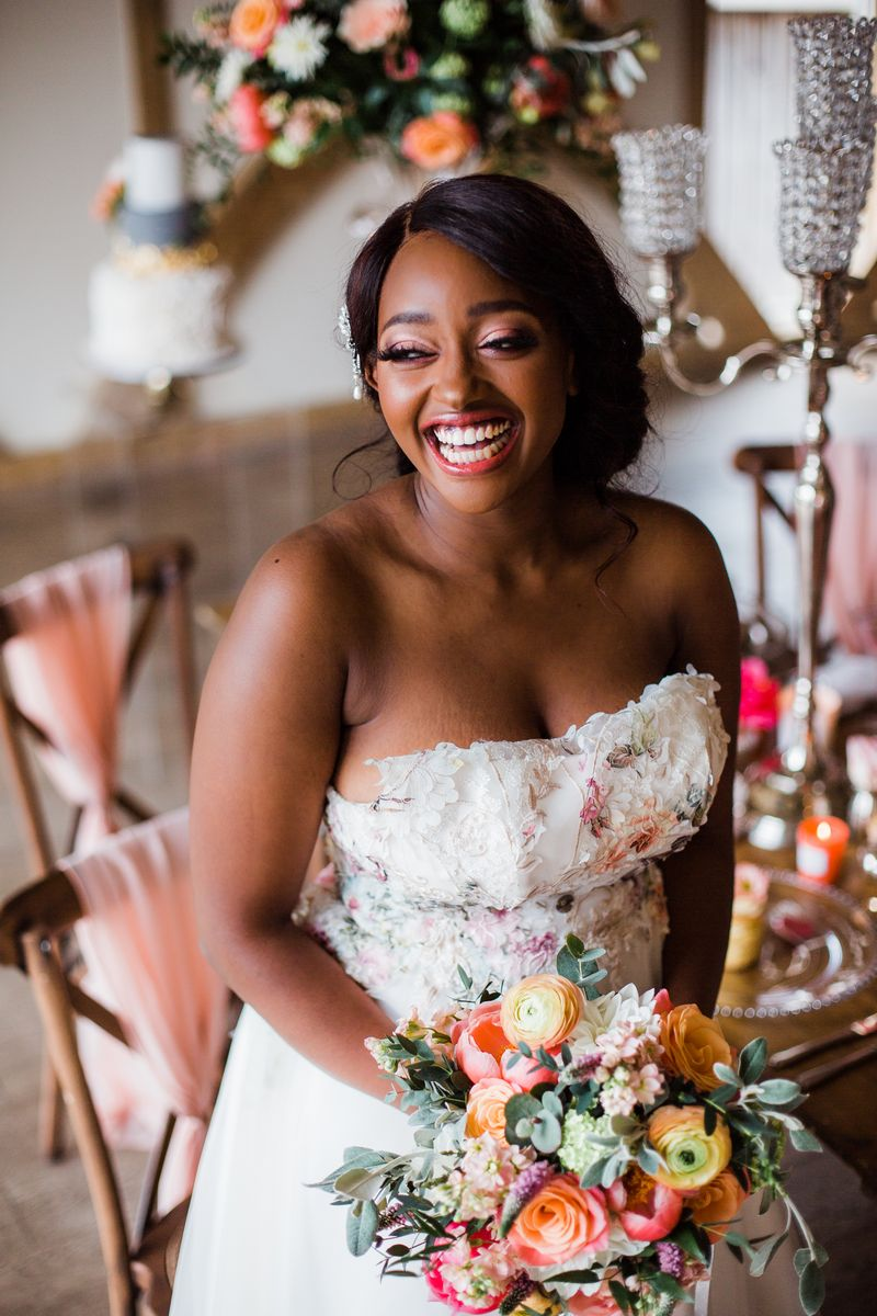 Bride with big smile sitting holding bouquet