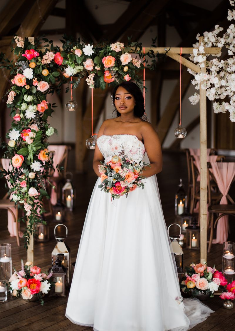 Bride holding bouquet in front of flower arch