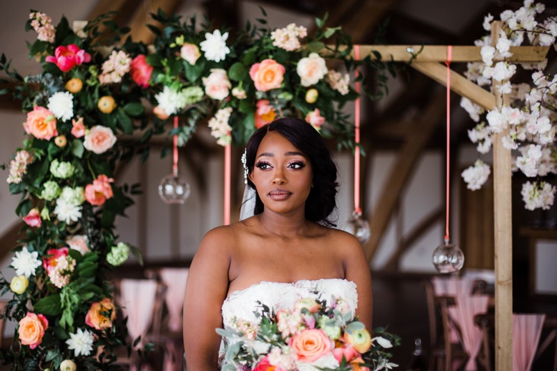 Bride standing in front of flower arch