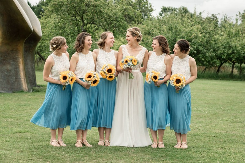 Bride with bridesmaids holding sunflower bouquets