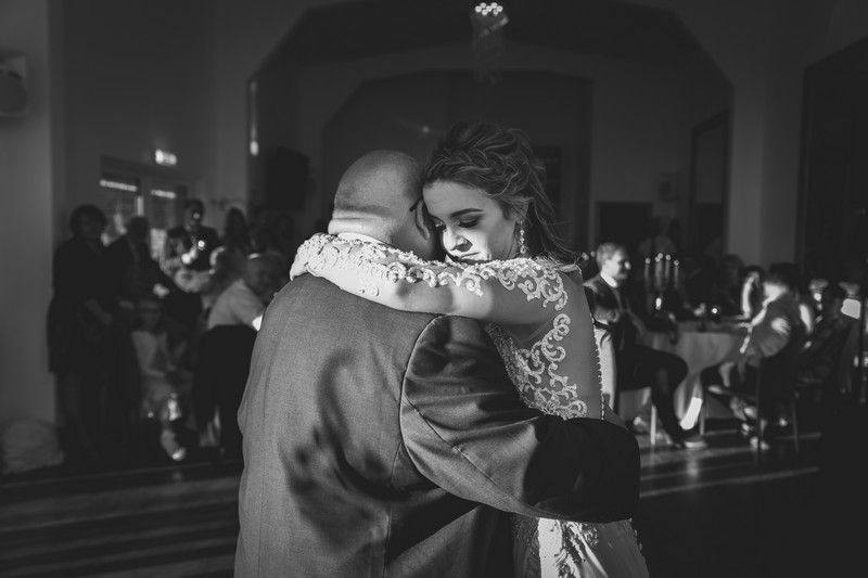 Bride hugging father on dance floor