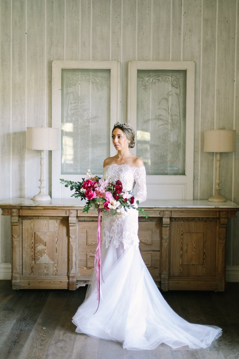 Bride standing holding burgundy and pink wedding bouquet