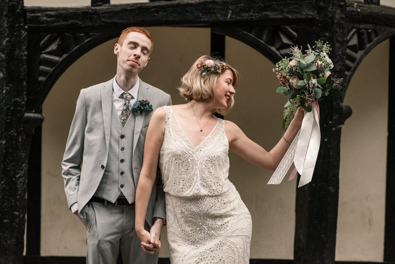 Bride holding bouquet to the side next to groom