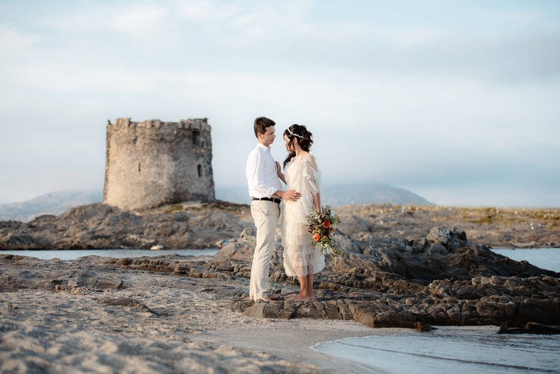 Bride and groom standing on La Pelosa beach with Torre della Pelosa in background