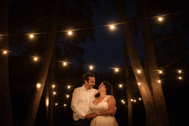 Bride and groom by trees at night under festoon lighting