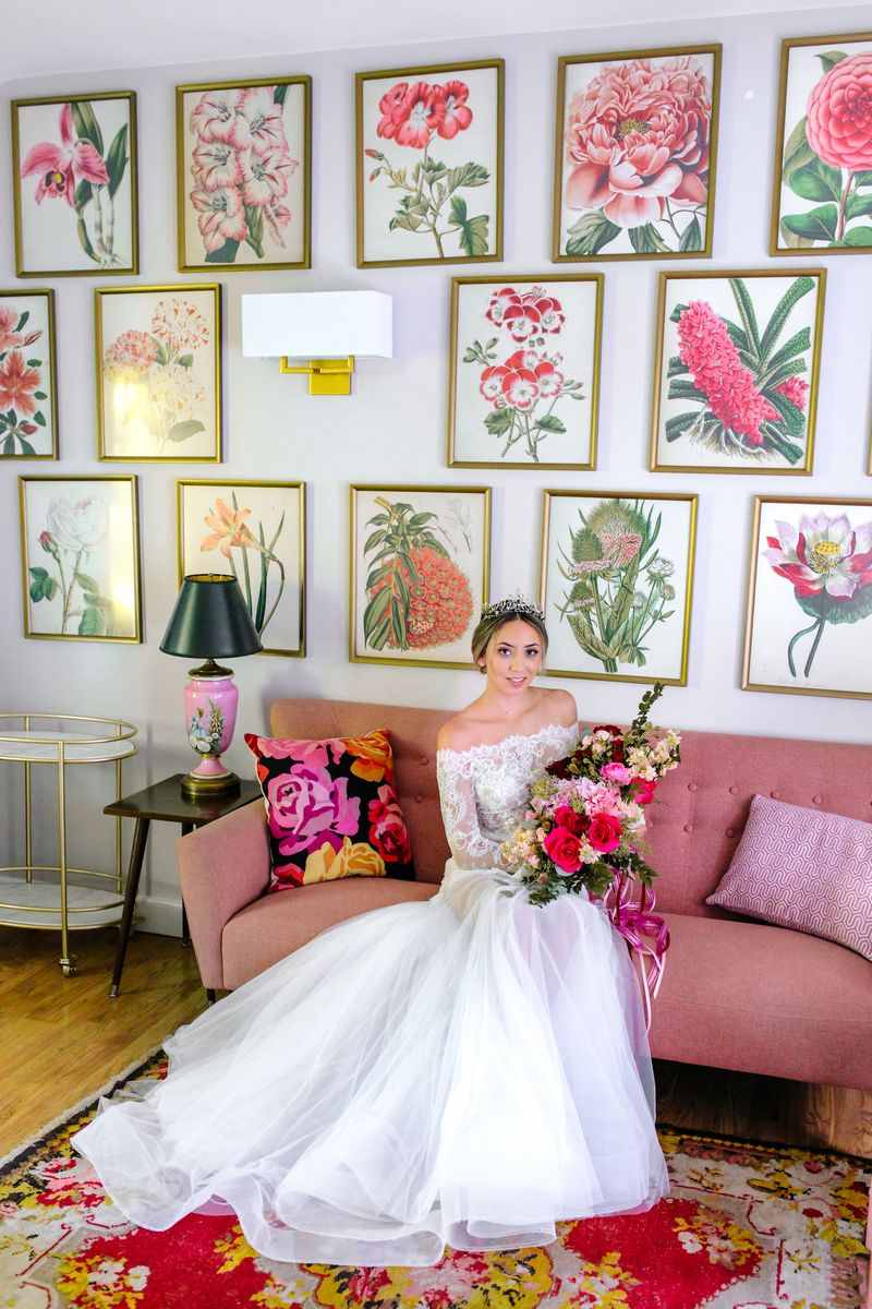Bride sitting on pink couch holding bouquet