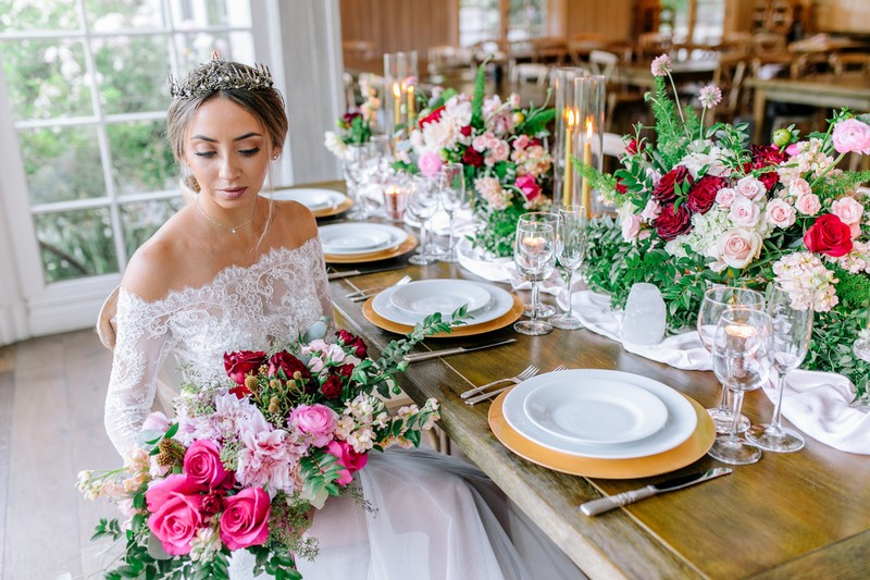 Bride sitting at wedding table holding burgundy and pink bouquet