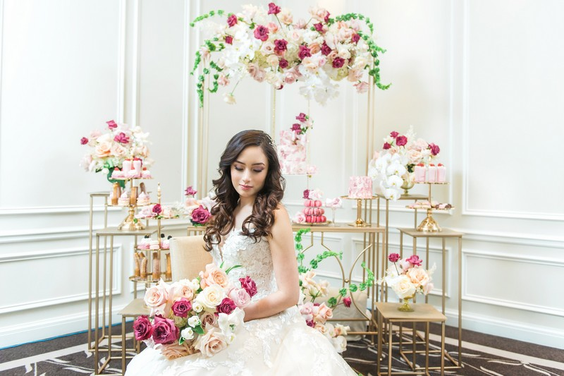 Bride sitting in front of dessert table styled with pink flowers