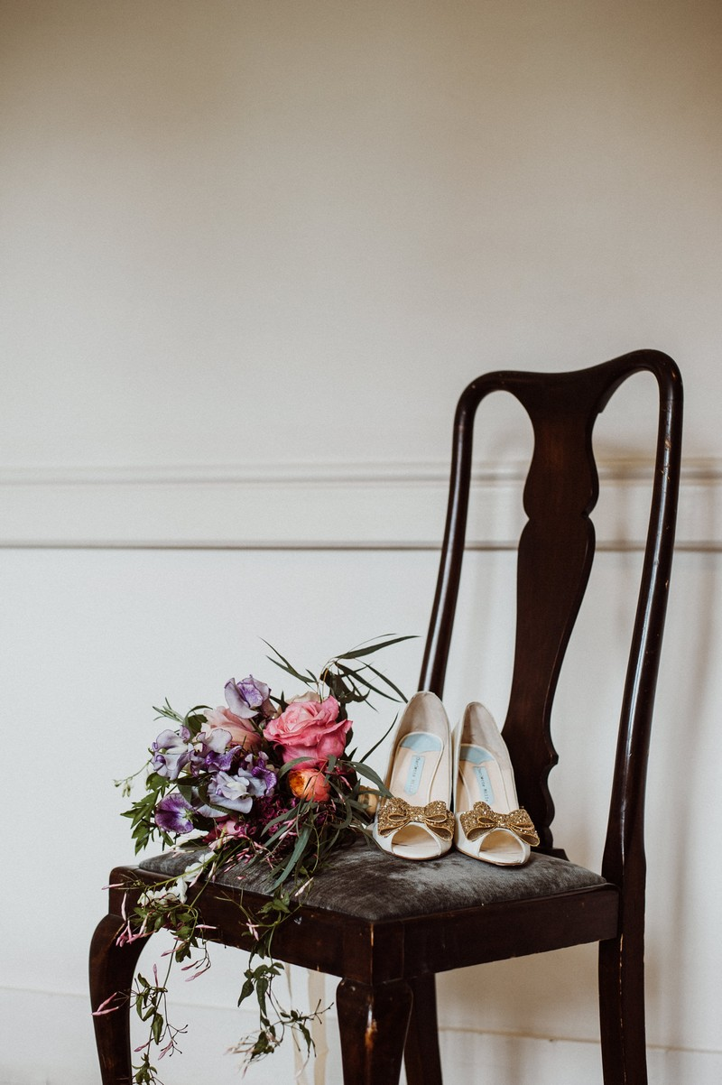 Bridal shoes and bouquet on chair