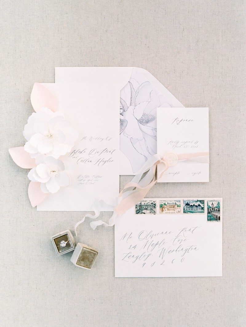 Elegant white wedding stationery with pink ribbon