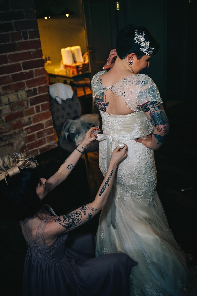 Lady with tattoos doing up back of bride's dress