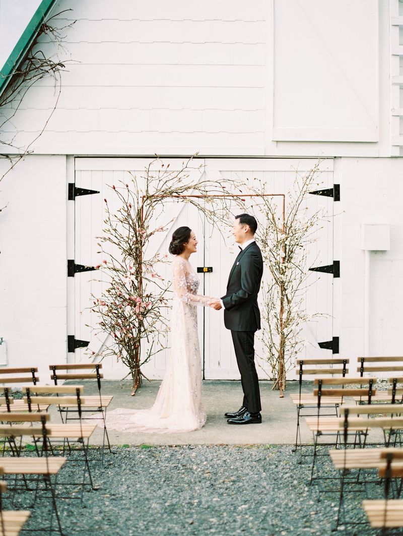 Bride and groom facing each other in front of magnolia floral ceremony arch