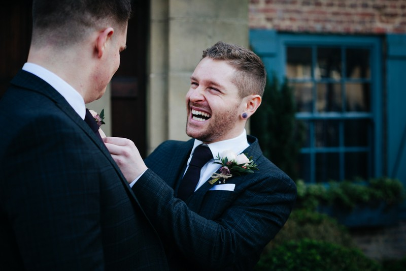 Groom with big smile as he adjusts best man's buttonhole