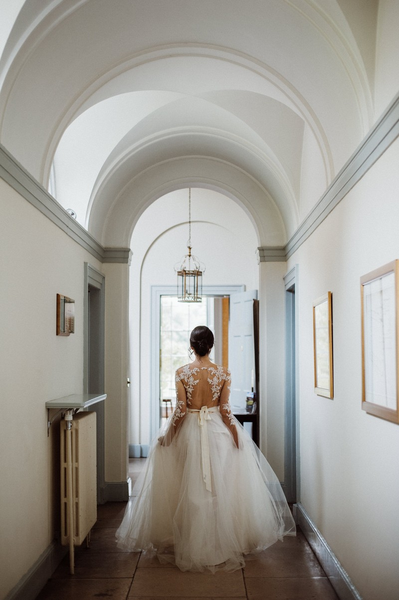 Bride walking through corridor at Fulham Palace