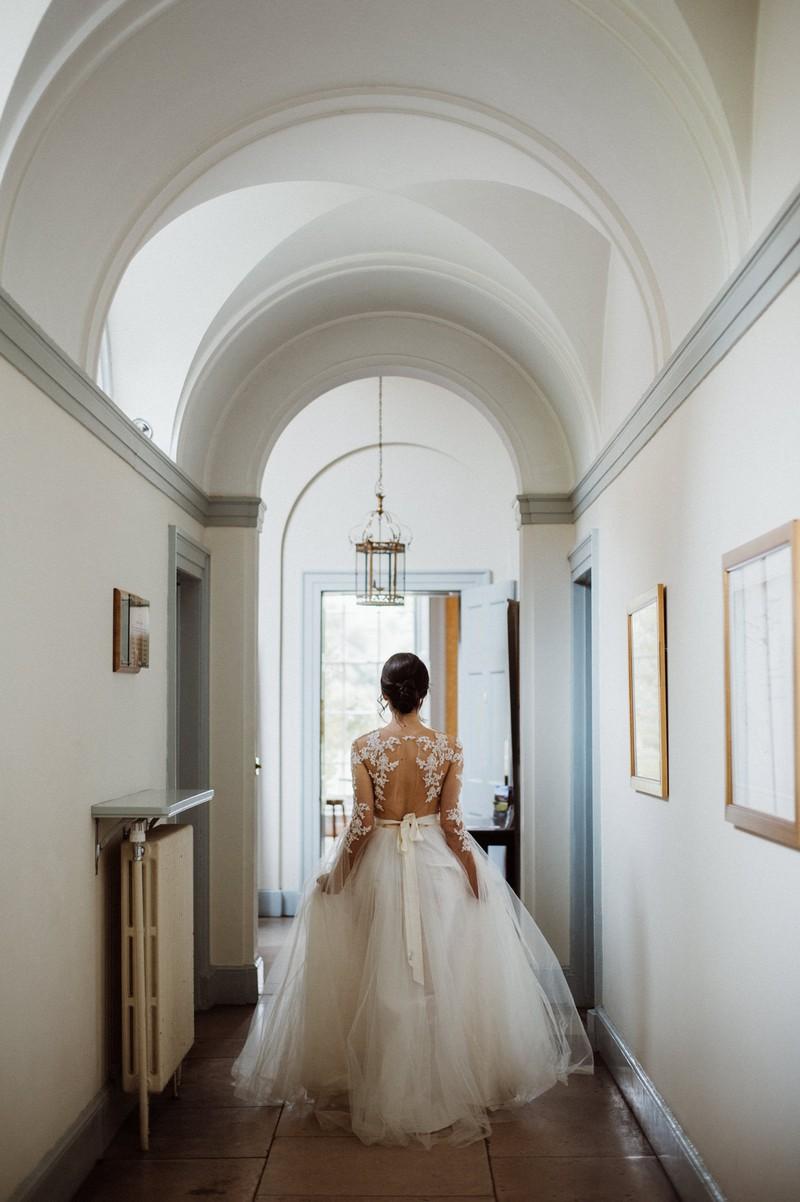 Bride walking through corridor at Fulham Palace