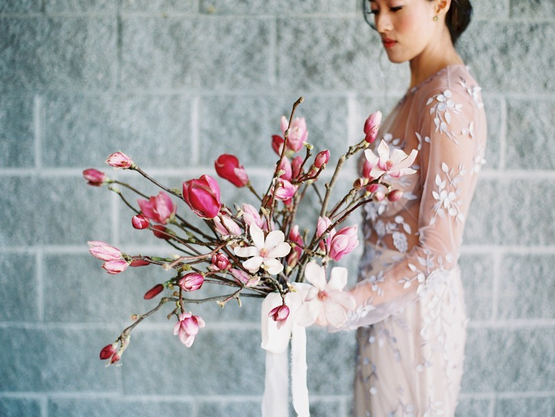 Bride holding large pink and white magnolia wedding bouquet