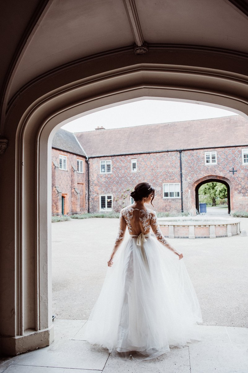 Bride standing at entrance to courtyard at Fulham Palace