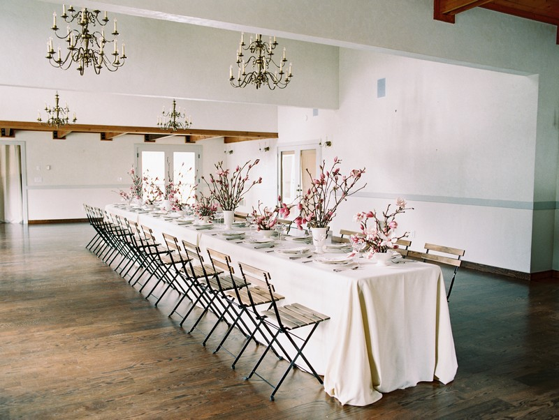 Long wedding table with white tablecloth topped with displays of pink magnolia