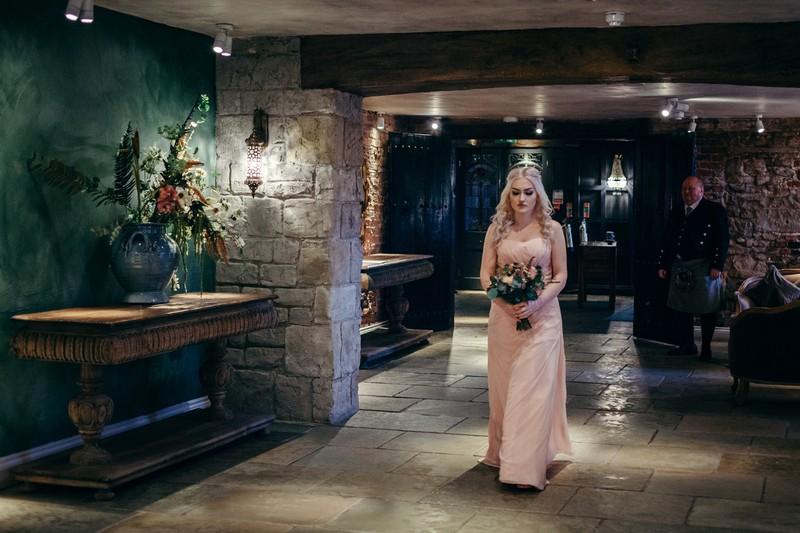 Bridesmaid walking down aisle at Le Petit Chateau