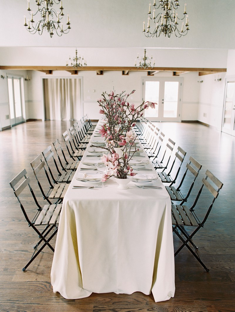 Long wedding table styled with pink magnolia