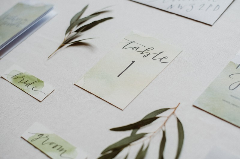 Simple wedding table number surrounded by leaves