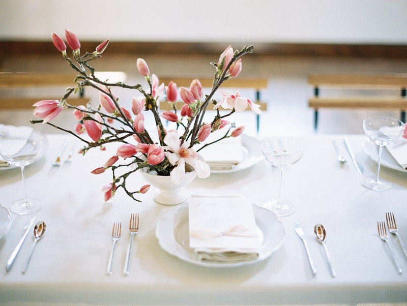 Wedding place setting with pink and white magnolia flowers