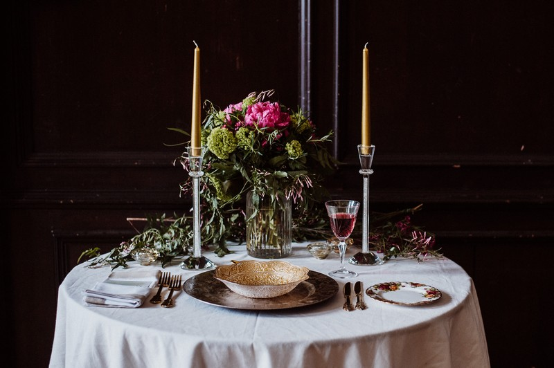 Small wedding table with tall candles and floral centrepiece