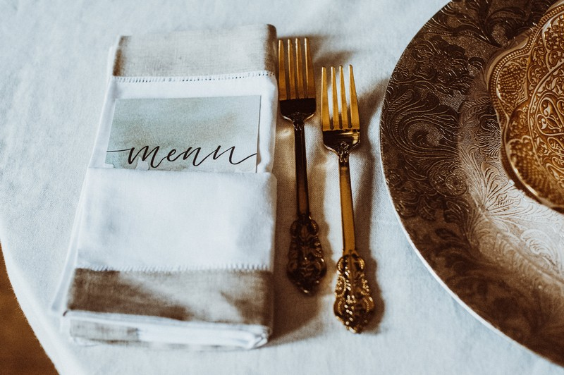 Wedding menu next to gold cutlery