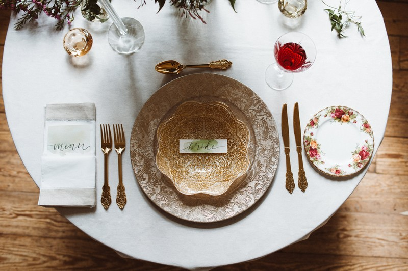 Wedding place setting with patterned plate and bowl, and gold cutlery
