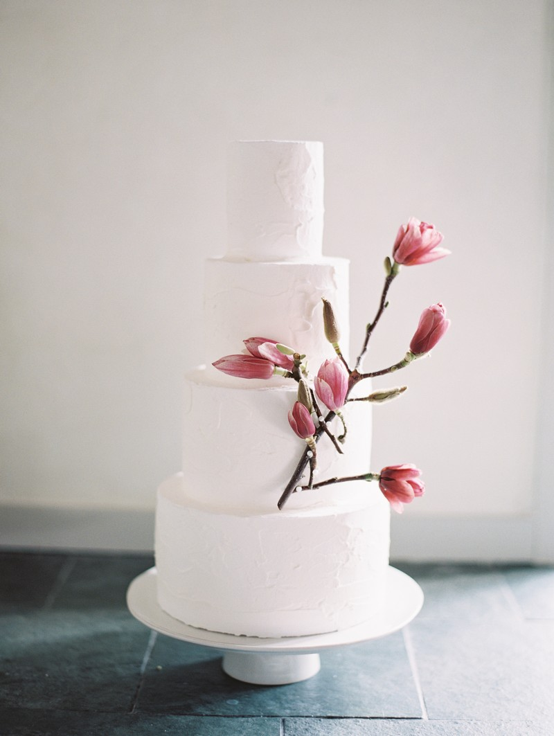 Wedding cake decorated with pink magnolia flowers