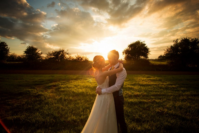 Bride and groom standing in field with arms around each other at sunset - Picture by Martin Dabek Photography