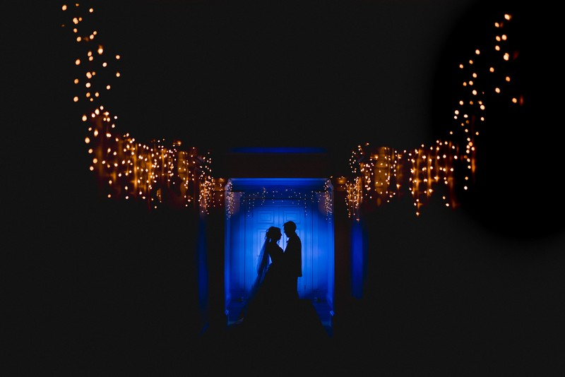 Silhouette of bride and groom against blue light background sourrounded by fairy lights - Picture by Murray Clarke