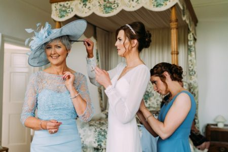 Bride combing mother's hair while bridesmaid does up the back of bride's dress - Picture by Eilidh Robertson Photography