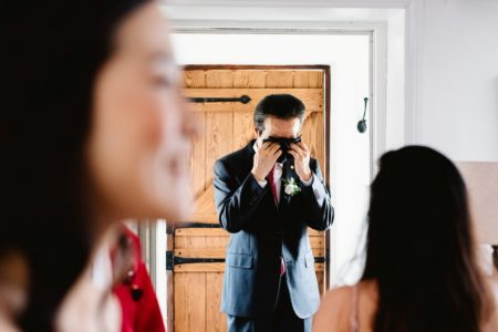 Emotional groom wiping tears from his eyes with a handkerchief - Picture by Fiona Kelly Photography