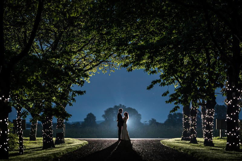 Bride and groom standing under trees at night - Picture by Rafe Abrook Photography