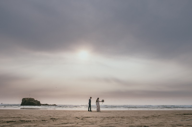 Bride and groom on beach under grey clouds - Picture by Ross Talling Photography