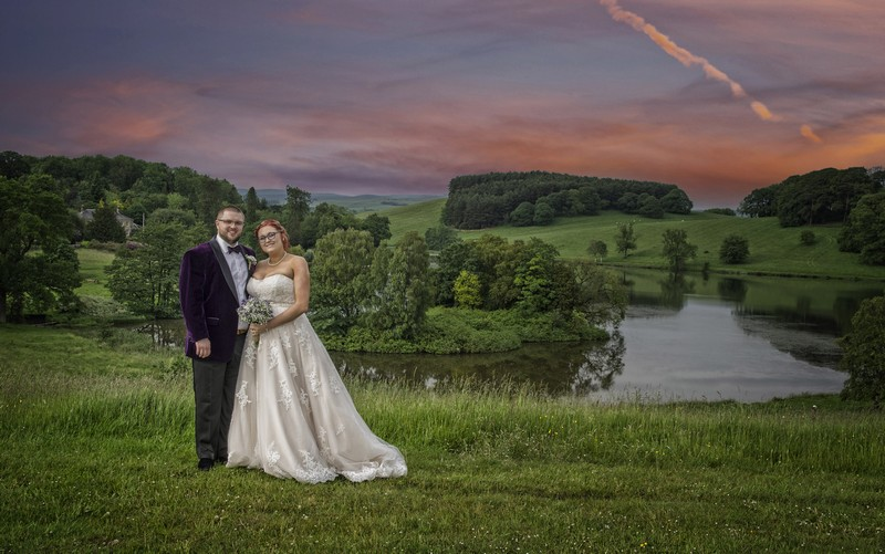Bride and groom in front of lake and red sky - Picture by Image-i-Nation Photography