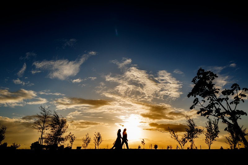 Silhouette of couple walking in front of brilliant yellow and blue sky from sunset - Picture by John Woodward Photography
