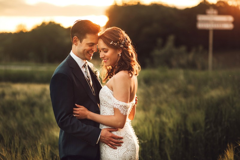 Bride and groom touching heads with field in background - Picture by Honeydew Moments