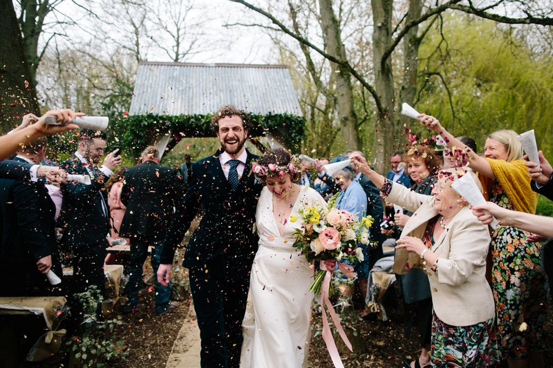 Bride and groom walking through shower of confetti - Picture by Dan Hough Photography