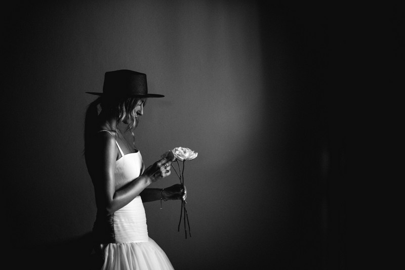 Bride wearing hat looking down at flower - Picture by That Moment Photo