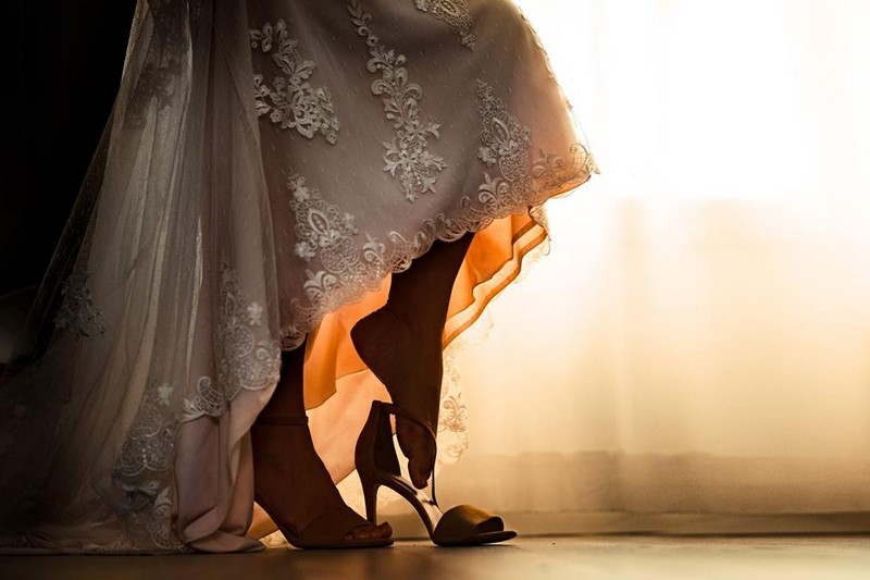 Bride putting foot into shoe - Picture by Vinson Images