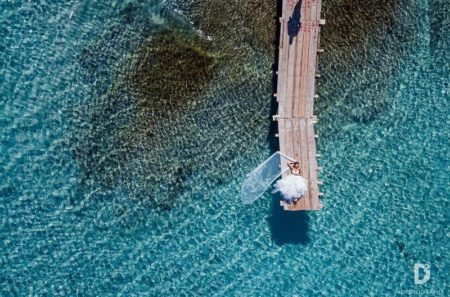 Bride lying down on end of jetty over bright blue sea - Picture by D2 Photography