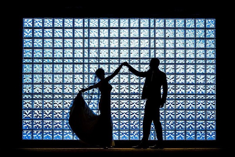 Silhouette of bride and groom against square glass wall - Picture by AV Fotoreportages