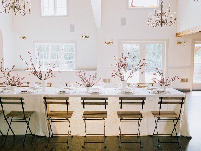 Wood and metal chairs at wedding table styled with pink and white magnolia flowers