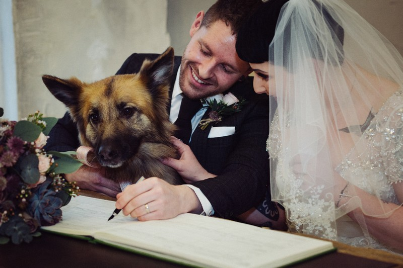 Groom signing register with dog there