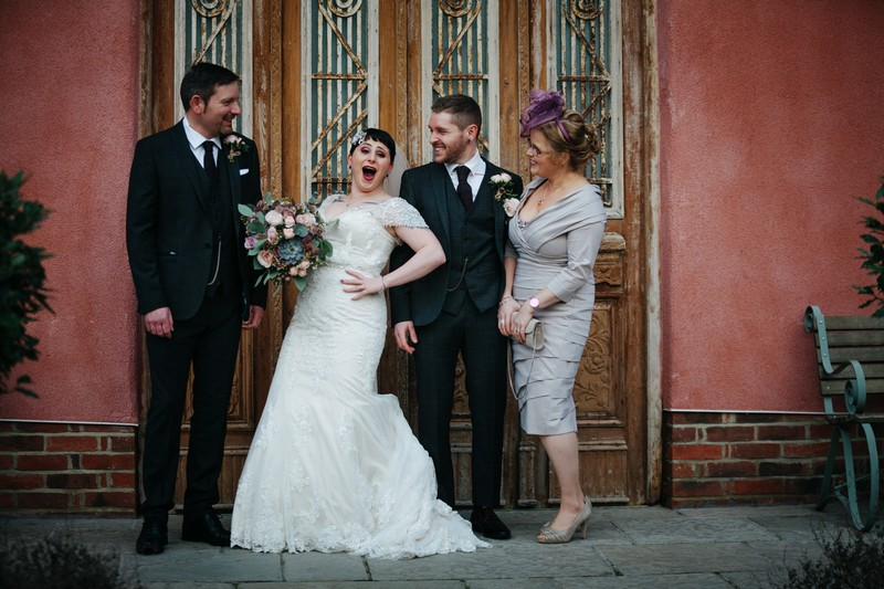 Bride with hand on hip during formal photographs