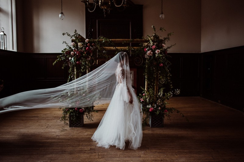 Bride with long veil walking past chuppah